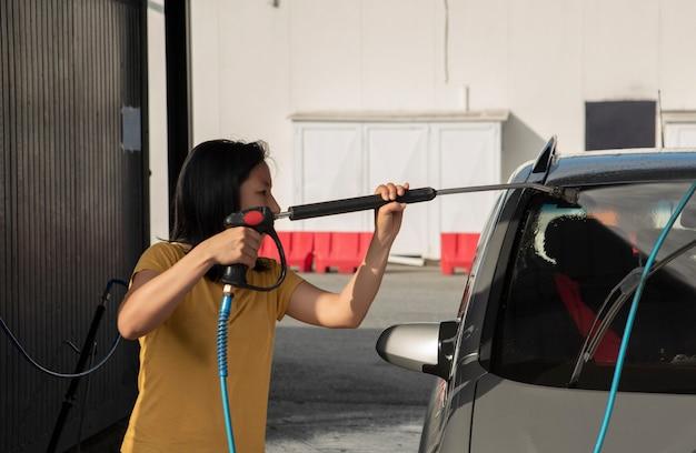 Kobieta myjąca samochód w myjni samochodowej