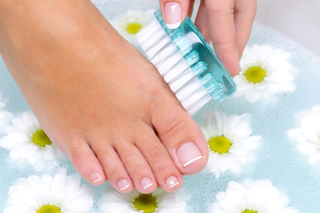 Kobieta myje i czyści paznokcie w wodzie za pomocą szczoteczki do czyszczenia