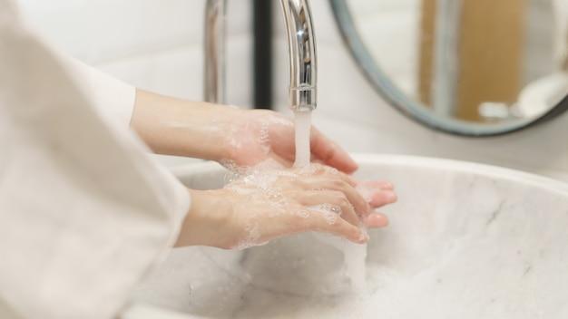 Kobieta myje jej ręki, ostrość palec