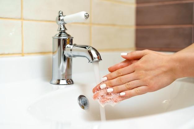 Kobieta myje jej ręki z mydła zakończeniem up