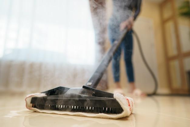 Kobieta myje podłogę mopem parowym.