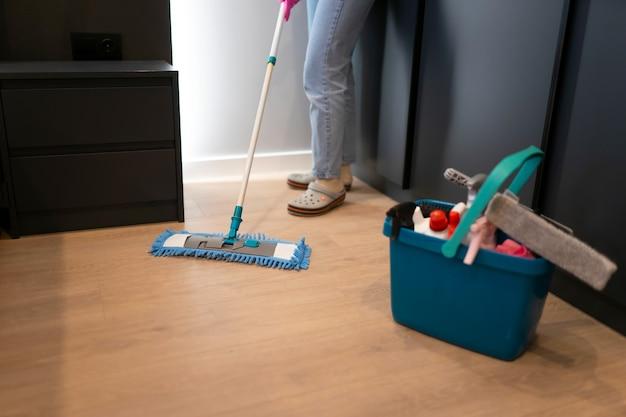 Kobieta myje podłogę w sypialni