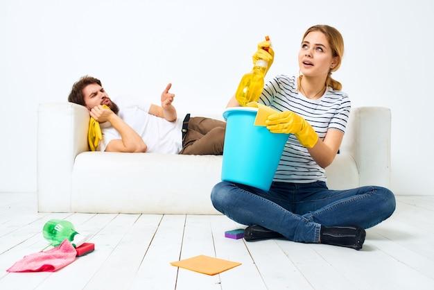 Kobieta myje podłogi, a mężczyzna siedzi na kanapie