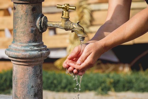 Kobieta myje ręce pod bieżącą wodą na ulicy