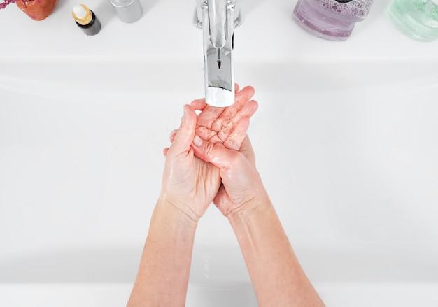 Kobieta myje ręce pod bieżącą wodą. pojęcie higieny, widok z góry, opieka zdrowotna. higiena osobista i pielęgnacja ciała