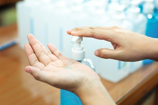 Kobieta myje ręce żelem do dezynfekcji rąk, aby zapobiec zakażeniu koronawirusem