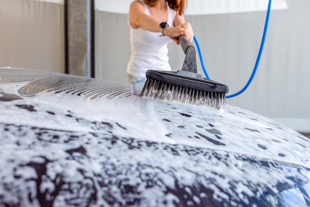 Kobieta myje samochód. kobieta w myjni samochodowej myje samochód szczotką z szamponem samochodowym. do reklamowania myjni samochodowej lub banera.