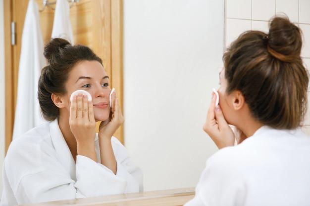 Kobieta myje twarz balsamem i wacikami