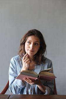 Kobieta myśli, czytanie książki.