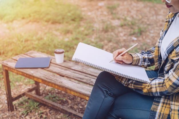 Kobieta myśli i pisze notatki na papierze w parku