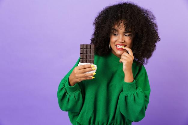 Kobieta na białym tle nad fioletową przestrzeń trzymając czekoladę.