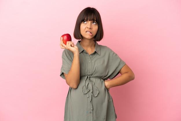 Kobieta na białym tle w ciąży i sfrustrowana, trzymając jabłko