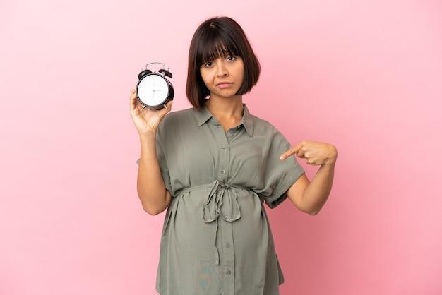 Kobieta na białym tle w ciąży i trzymająca zegar z zestresowanym wyrazem twarzy
