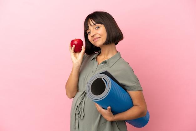 Kobieta na białym tle w ciąży trzyma jabłko i idzie na zajęcia jogi