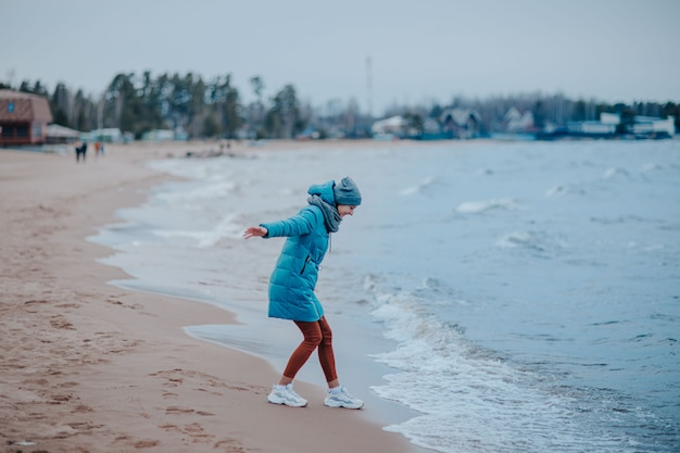 Kobieta na brzegu morza w burzy. wybrzeże morza z błękitną wodą. fale na linii wybrzeża, kobieta spacerująca po plaży.