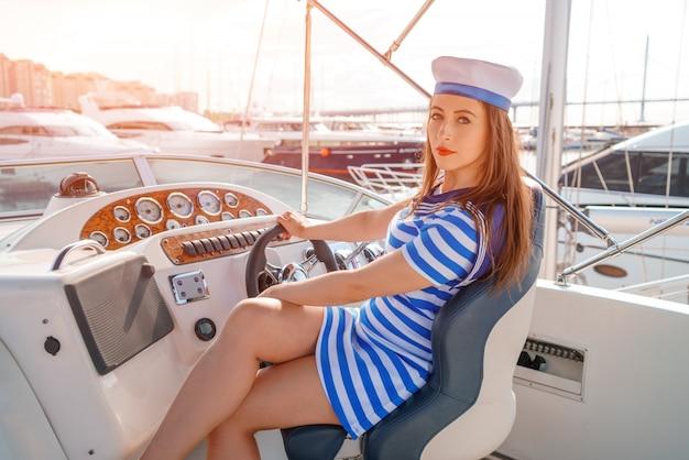 Kobieta na czele jachtu w sukience w paski