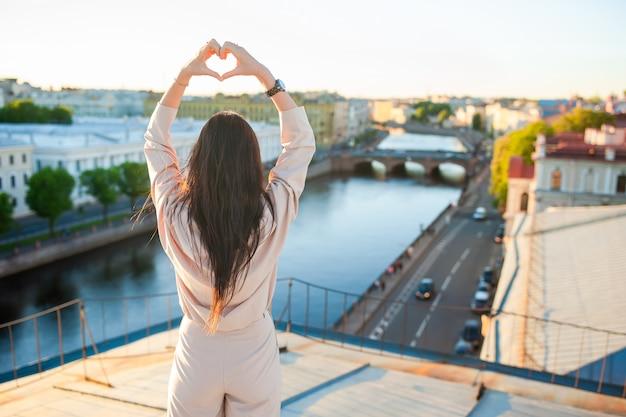 Kobieta na dachu cieszy się z widokiem pięknego zmierzchu w świętym petersburg w rosja