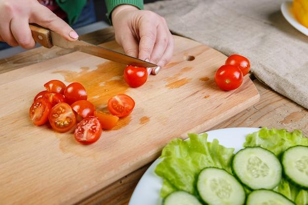 Kobieta na desce do krojenia tnie pomidory koktajlowe w plasterki na sałatkę warzywną. przedni widok