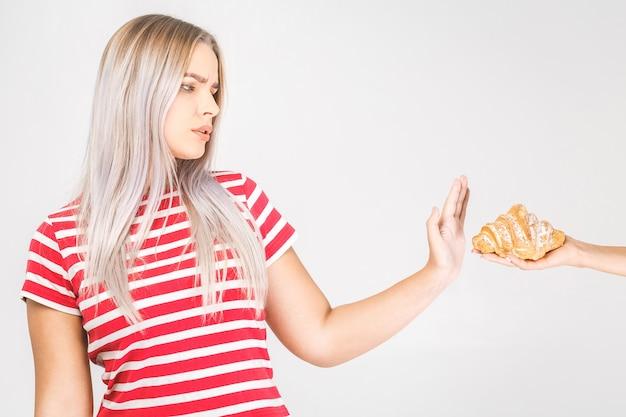 """Kobieta na diecie dla dobrego pojęcia zdrowia. kobieta robi znak """"nie"""", żeby odmówić fast foodów lub fast foodów zawierających dużo tłuszczu."""