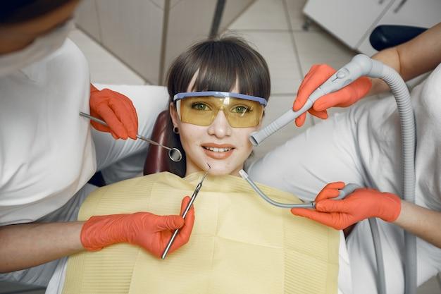 Kobieta na fotelu dentystycznym. dziewczyna jest badana przez dentystę, a dentyści leczą jej zęby