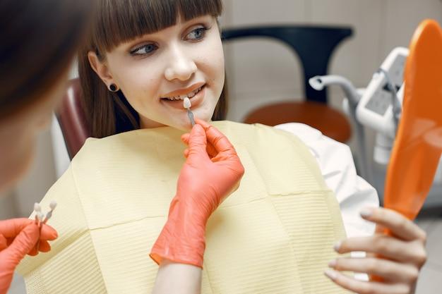 Kobieta na fotelu dentystycznym. dziewczyna wybiera implant. piękno leczy zęby