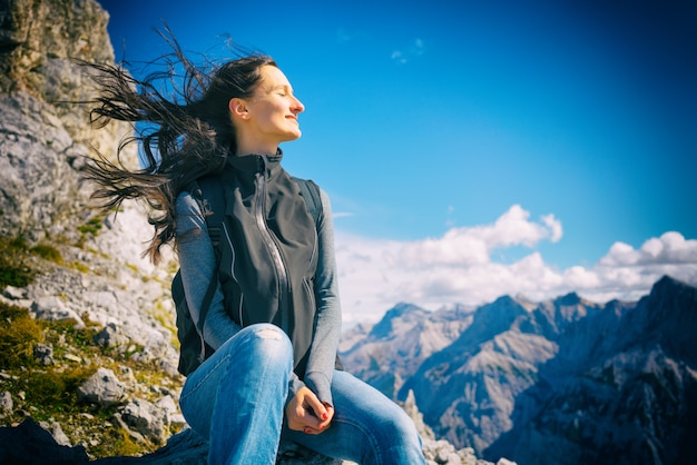 Kobieta na górskiej wędrówce odpoczynku, jej włosy wieje wiatr