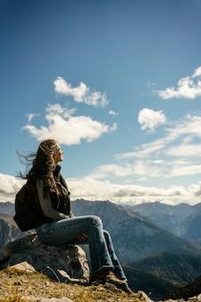 Kobieta na górskiej wycieczce o odpoczynku siedzi na skale patrząc na dolinę