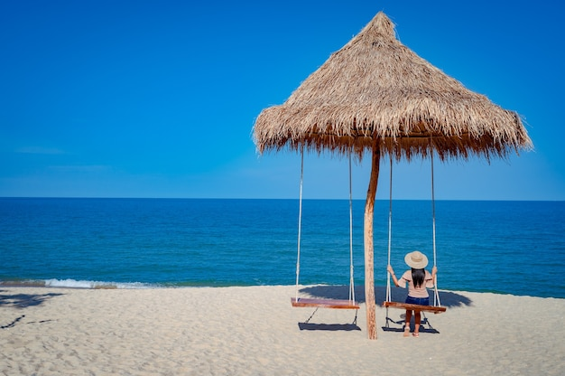 Kobieta na huśtawce pod drewnianą chatą przy plaży na plaży sichon, nakhon si thammarat