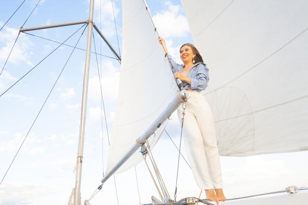 Kobieta na jachcie przed żaglami nieba i morza. pojęcie żeglarstwa i wakacji nad morzem.