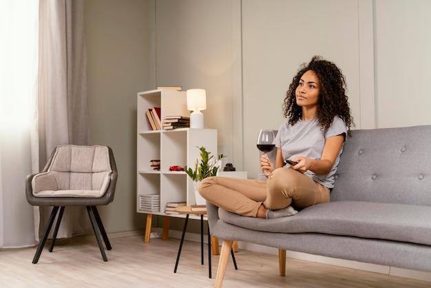 Kobieta na kanapie oglądaniem telewizji i piciem wina