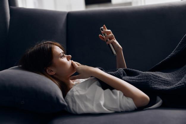 Kobieta na kanapie patrząc na ekran telefonu komórkowego i miękką poduszkę.
