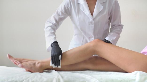 Kobieta na kanapie, przygotowując się do depilacji