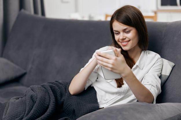 Kobieta na kanapie z telefonem komórkowym w ręku komfort w pomieszczeniach