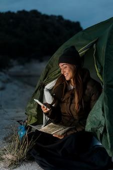 Kobieta na kempingu i przy użyciu telefonu komórkowego