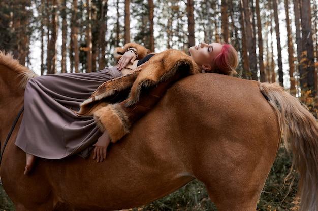 Kobieta na koniu jesienią. kreatywny jasny różowy makijaż na twarzy dziewczyny, farbowanie włosów. portret dziewczynki z koniem. jazda konna w jesiennym lesie. jesienne ubrania