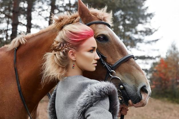 Kobieta na koniu jesienią. kreatywny jasny różowy makijaż na twarzy dziewczyny, farbowanie włosów. portret dziewczynki z koniem. jazda konna w lesie jesienią. jesienne ubrania