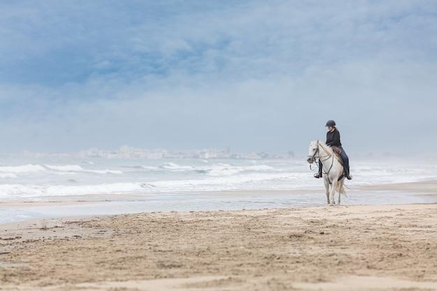 Kobieta na koniu na plaży w pochmurny dzień