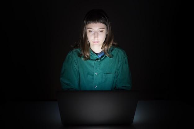 Kobieta na laptopie w pomieszczeniu późnym wieczorem