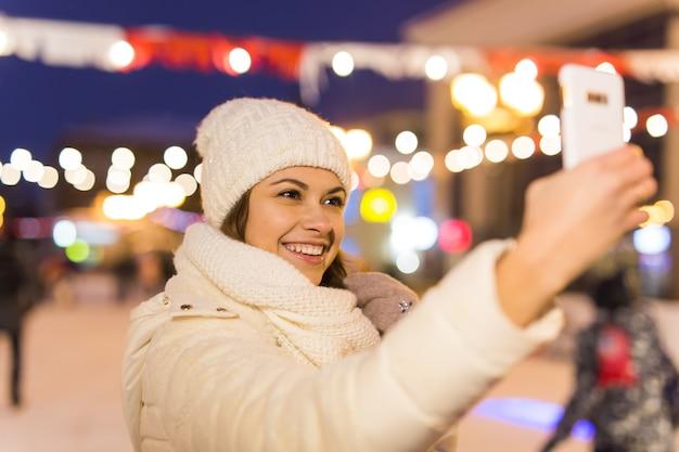 Kobieta na lodowisku jeździ na łyżwach i robi selfie na smartfonie sylwestra i wróżka bożonarodzeniowa