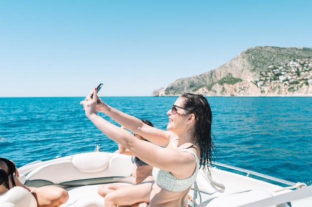 Kobieta na łodzi robi selfie smartfonem