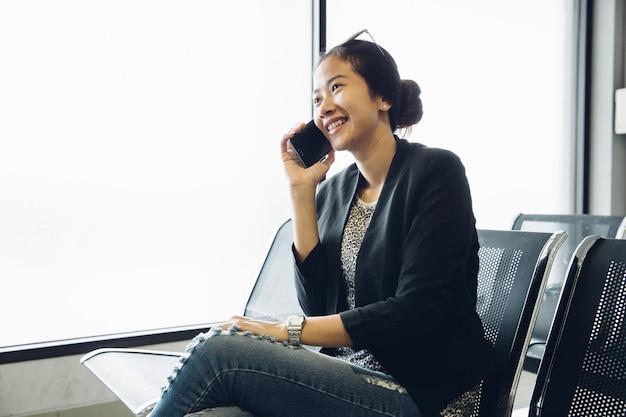 Kobieta na lotnisku, czekając na podróż samolotem za pomocą inteligentnego telefonu