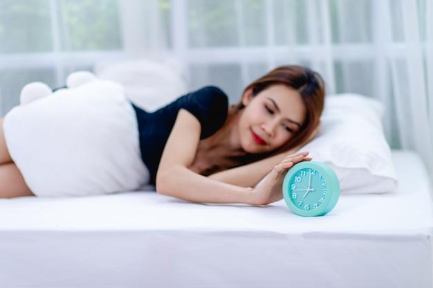 Kobieta na łóżku z niebieskim budzikiem