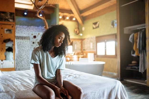 Kobieta na łóżku z telefonem komórkowym