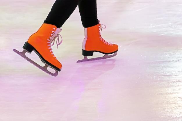 Kobieta na łyżwach. zima na zewnątrz na lodowisku. lód i nogi. pomarańczowe łyżwy damskie z odbiciem na białym lodzie.
