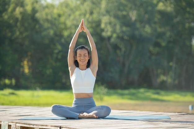 Kobieta na macie do jogi na relaks w parku nad jeziorem górskim. spokojna kobieta z zamkniętymi oczami uprawiająca jogę, siedząca w pozie padmasana na macie, ćwiczenia lotosu, atrakcyjna sportowa dziewczyna w sportowym stroju.