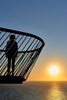 Kobieta na moście oglądając wschód słońca nad morzem