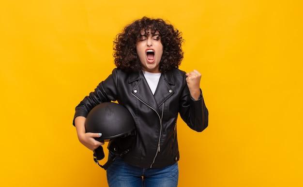 Kobieta na motocyklu krzycząca agresywnie z gniewnym wyrazem twarzy