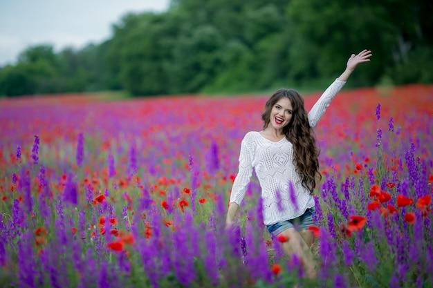 Kobieta na naturze w polu z purpurowymi kwiatami