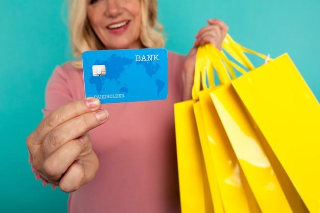 Kobieta na niebieskiej ścianie trzyma kartę kredytową i wiele żółtych toreb na zakupy.