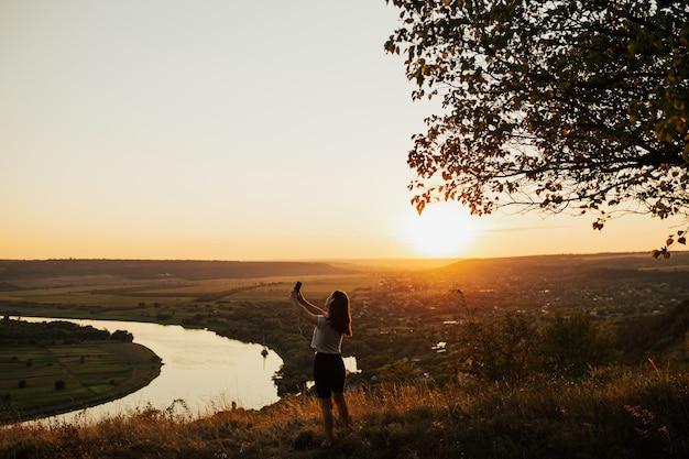 Kobieta na niesamowity zachód słońca latem. dziewczyna przy selfie na górski punkt widokowy.
